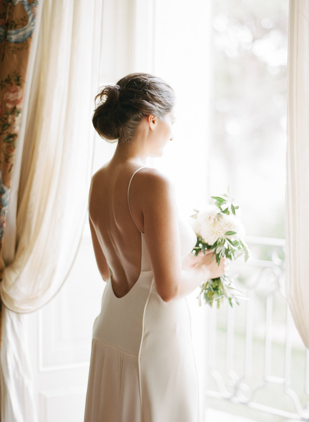 A bride holds her bouquet at the window of a chateau in Provence, France; Sylvie Gil Photography