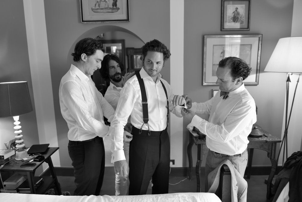 Groomsmen help the groom with his cufflinks and suspenders; Sylvie Gil Photography