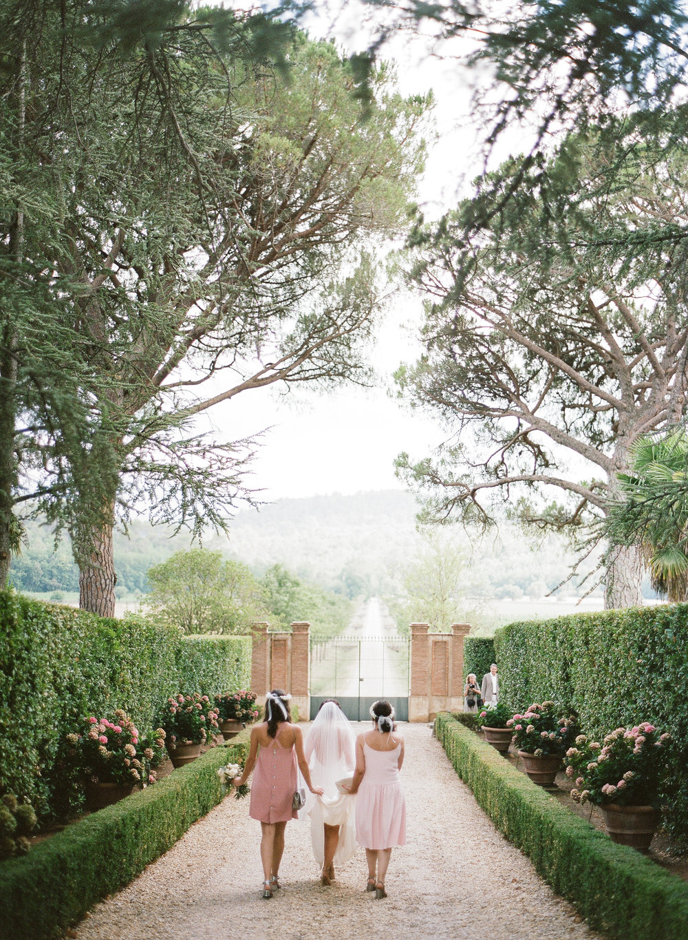The bridesmaids walk the bride through the chateau grounds to the ceremony; Sylvie Gil Photography