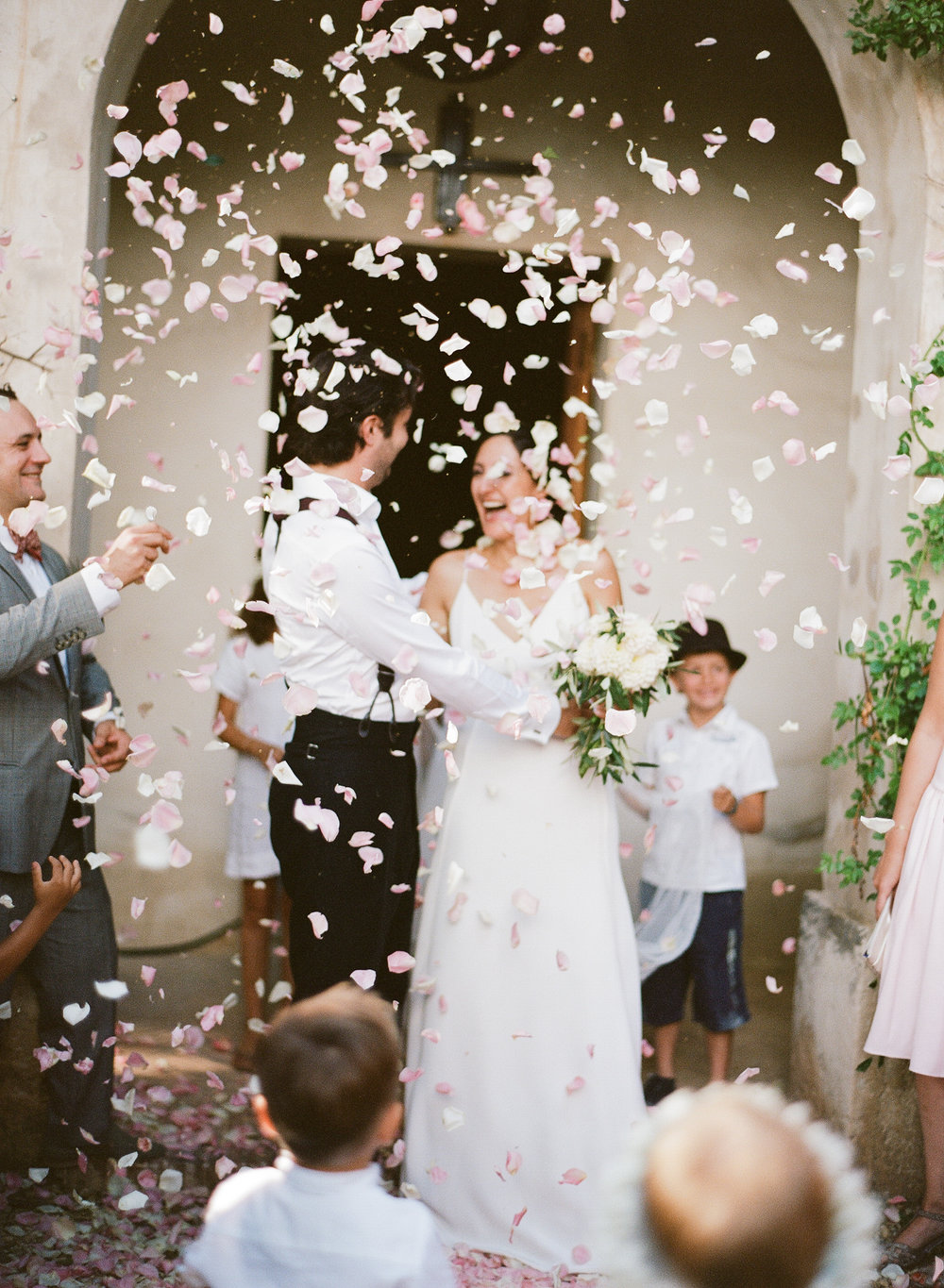 Bride and groom just married, the village guests throw rose petals; Sylvie Gil Photography