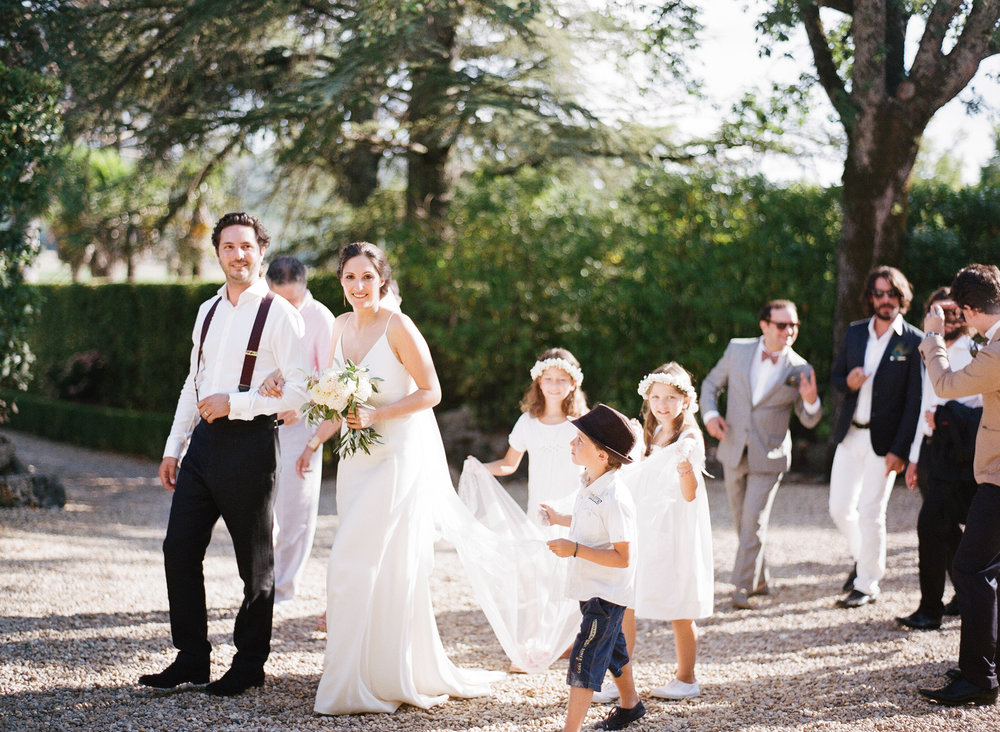 Bride and groom walk out of the Provence village chapel with flower girls and guests; Sylvie Gil Photography