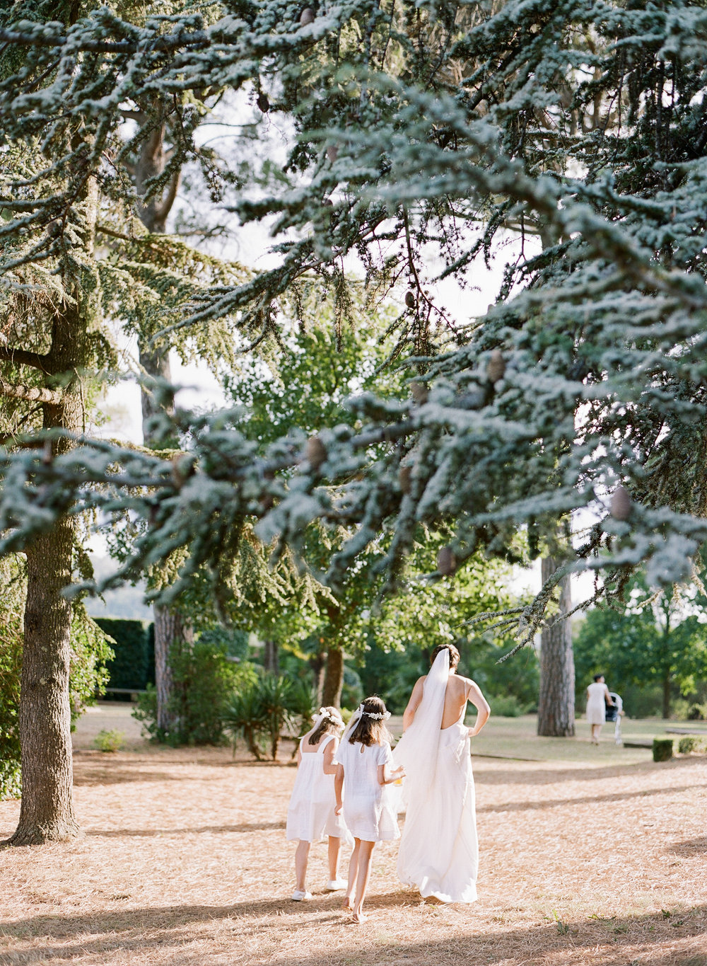 The bride walks through the Provence chateau grounds with flower girls; Sylvie Gil Photography