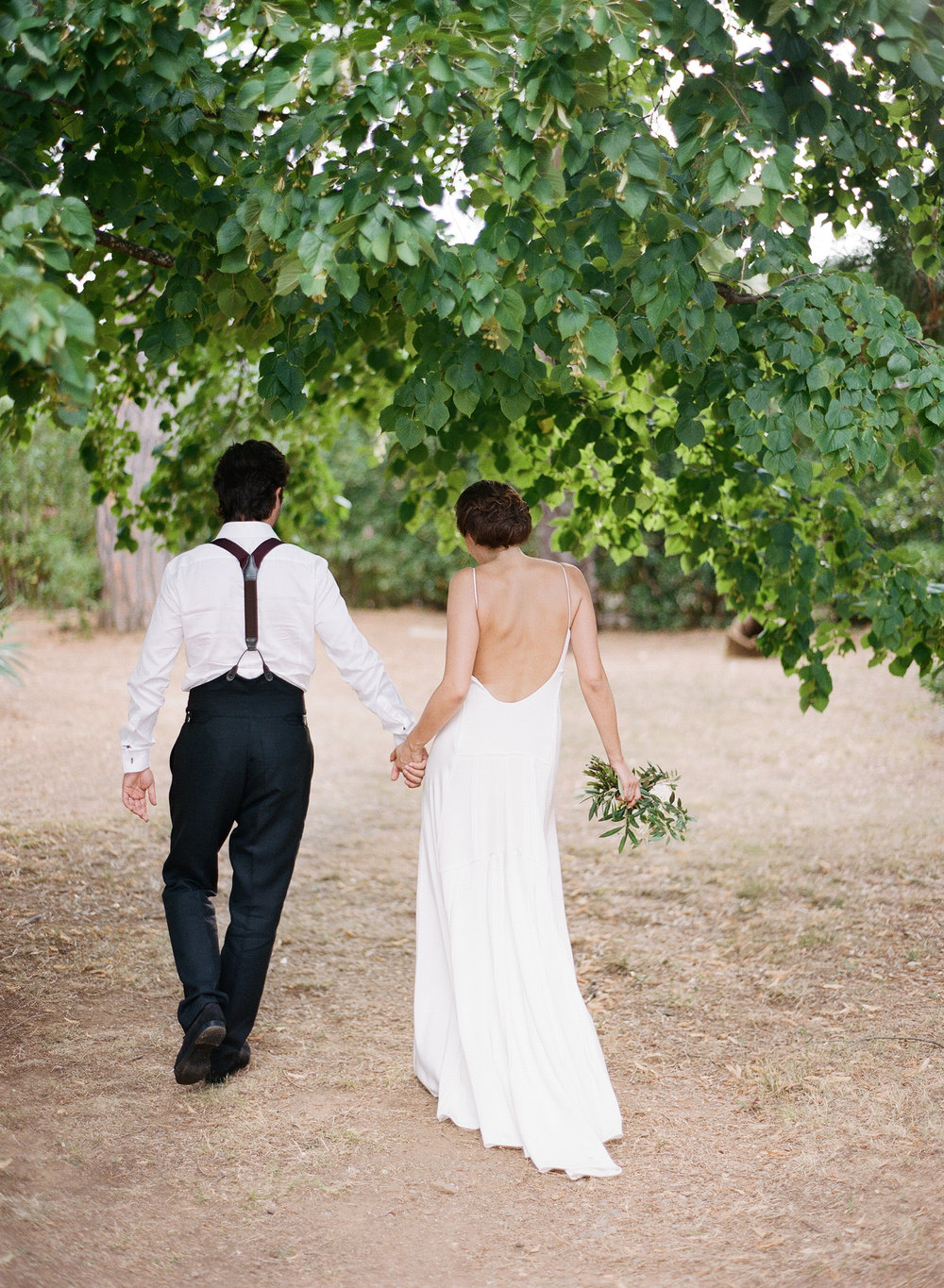 The bride and groom walk in the chateau grounds after the wedding ceremony; Sylvie Gil Photography