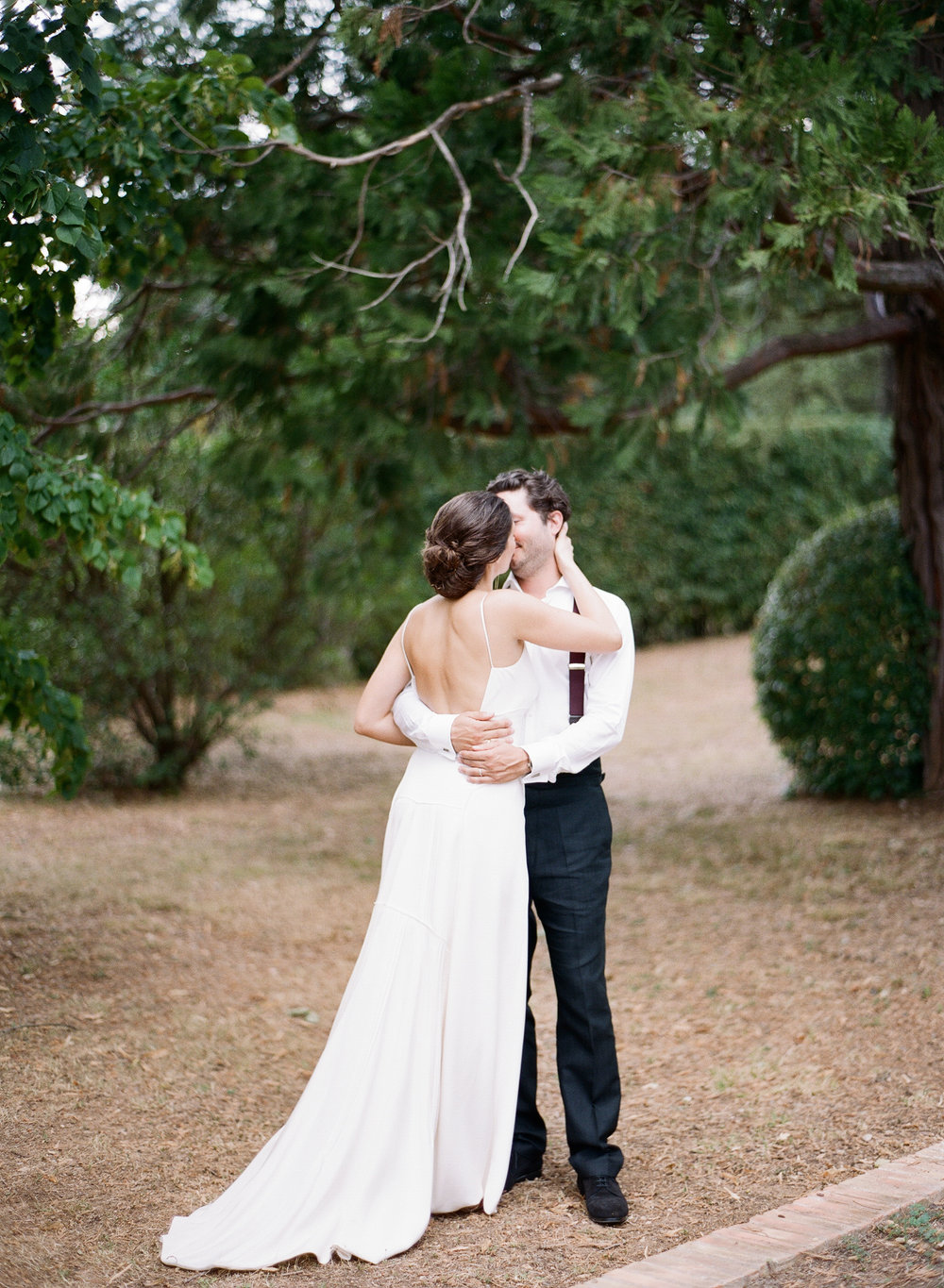 Bride and groom share a kiss in the chateau gardens; Sylvie Gil Photography