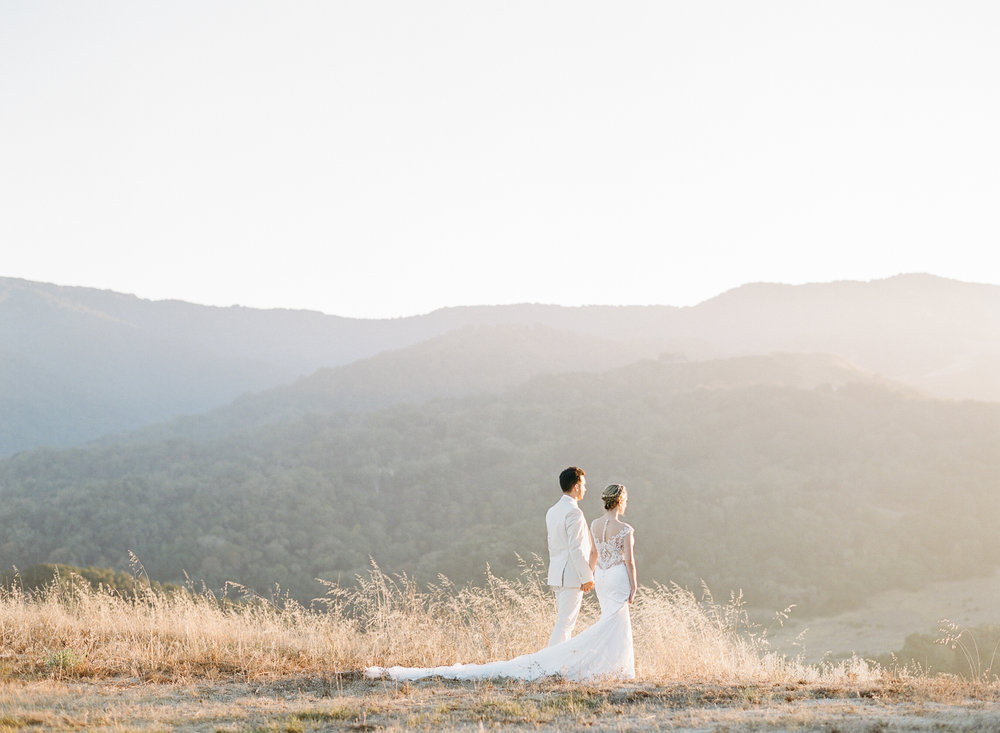 Bride and groom look into the sunset in the hills of Santa Lucia Preserve; Sylvie Gil Photography