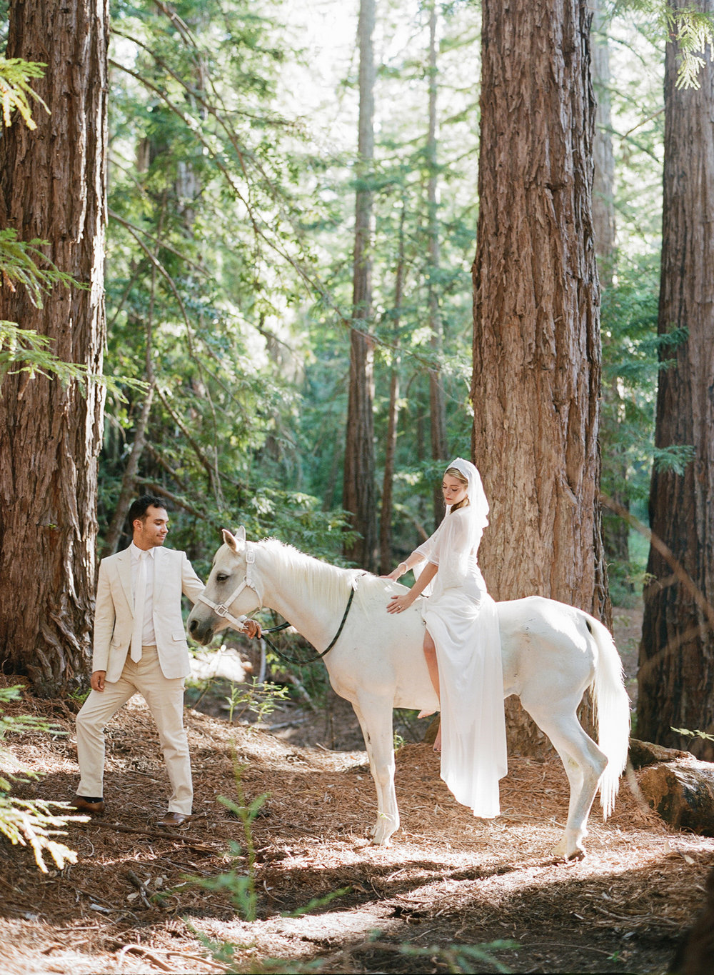 The bride sits on a white horse with the groom after the ceremony; Sylvie Gil Photography