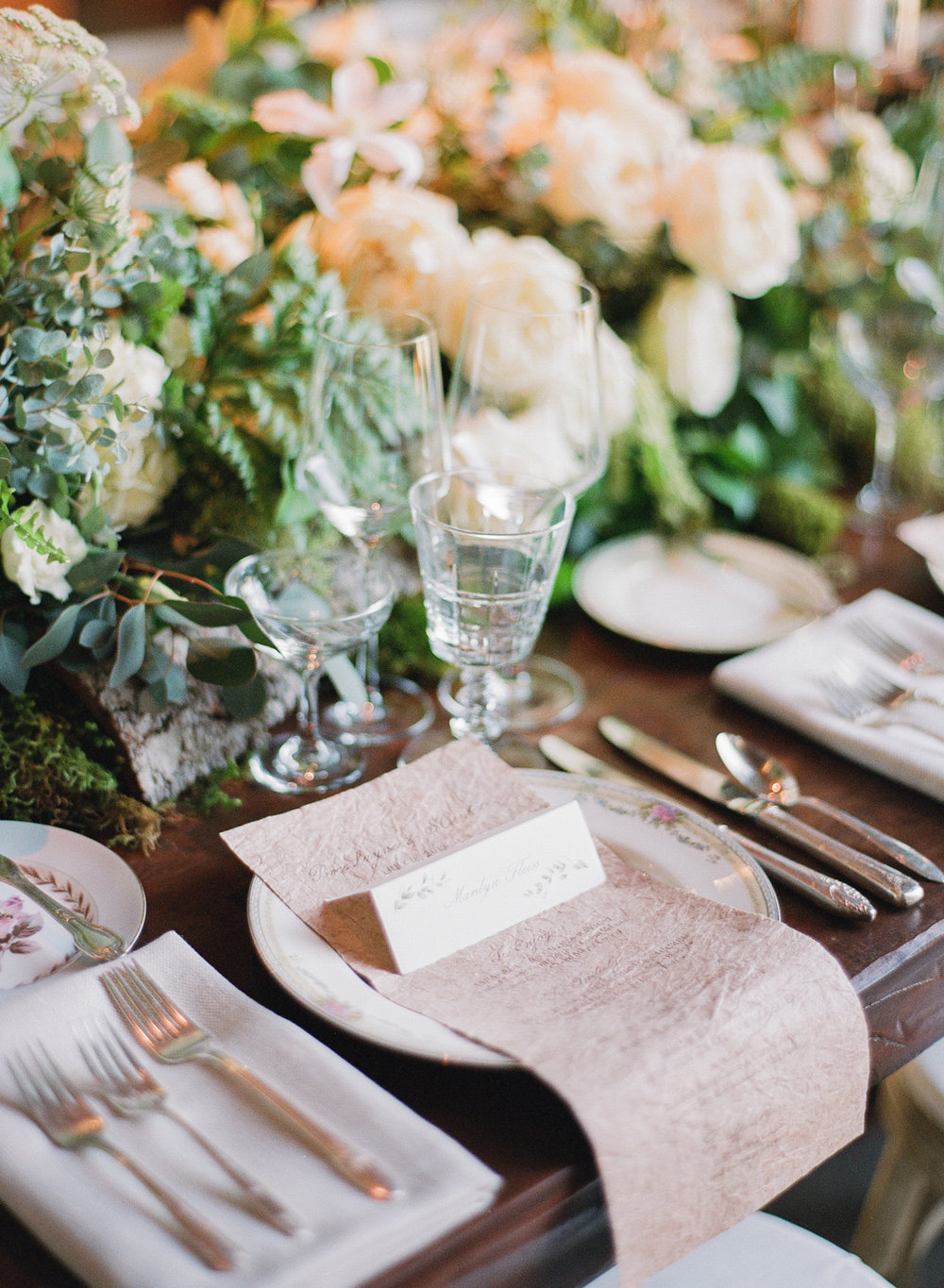 Leafy, rustic reception tables set with ivory and beige settings; Sylvie Gil Photography