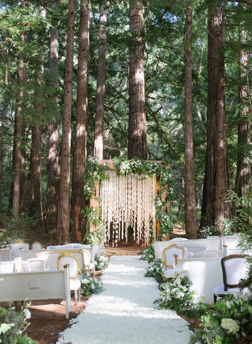 Vintage seating set up among the redwoods for a wedding ceremony in the Santa Lucia Preserve in Carmel, California; Sylvie Gil Photography