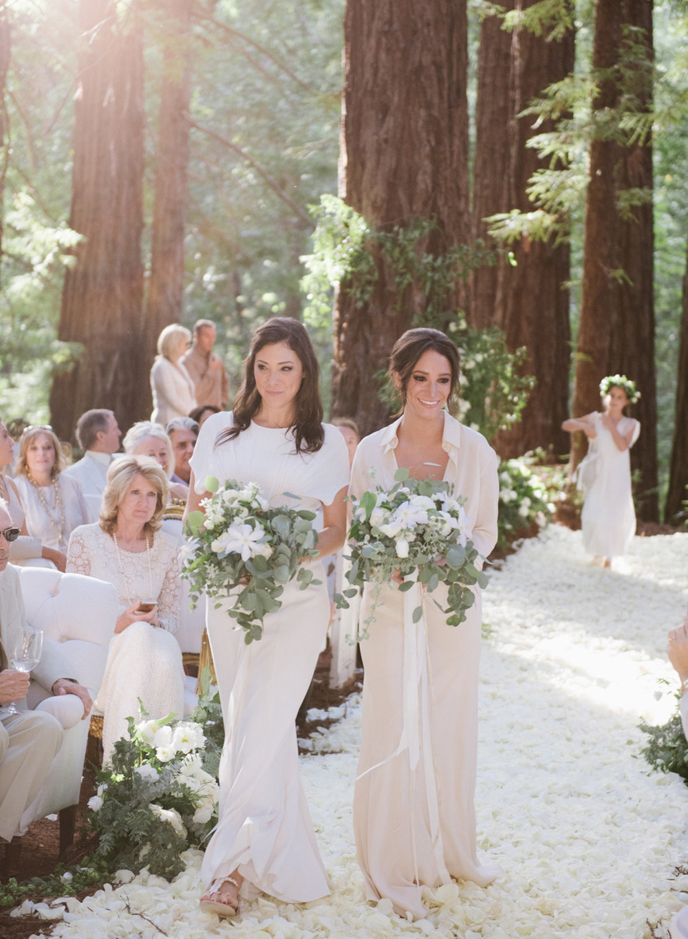 Bridesmaids with eucalyptus bouquets walk up the flower petal strewn aisle among the redwoods in Santa Lucia Preserve; Sylvie Gil Photography