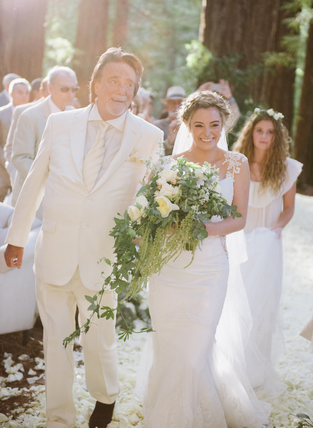 The bride walks up the aisle with her father among the redwoods at the Santa Lucia Preserve; Sylvie Gil Photography