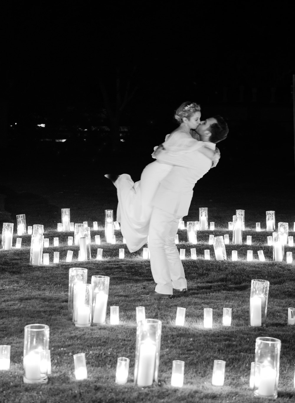 The bride and groom share a kiss among the pillar candles decorating a pasture at the Santa Lucia Preserve; Sylvie Gil Photography