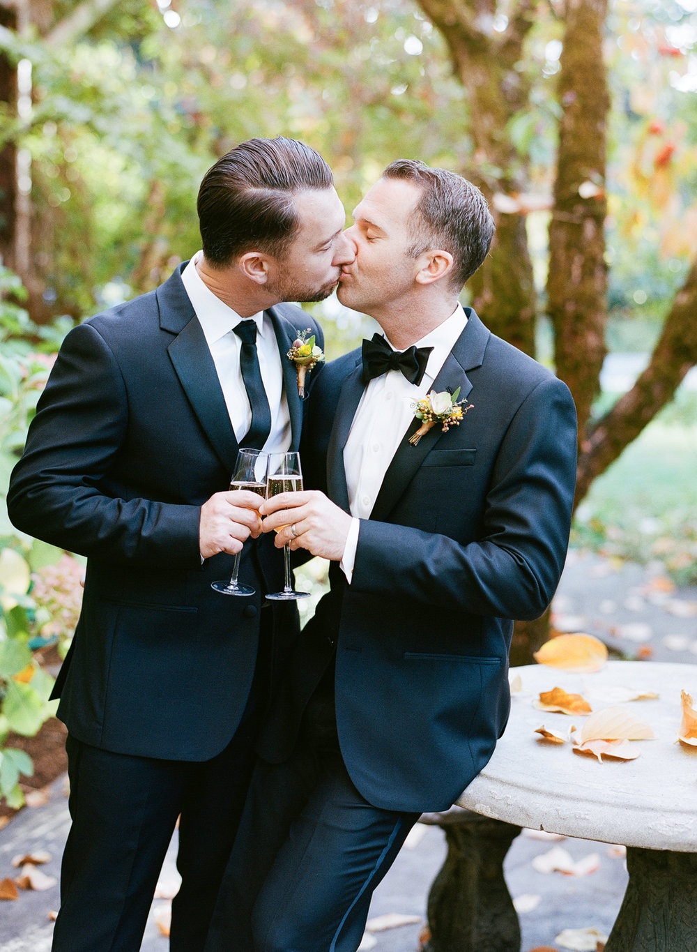 Grooms share a kiss and toast champagne after their wedding ceremony in St. Helena; Sylvie Gil Photography