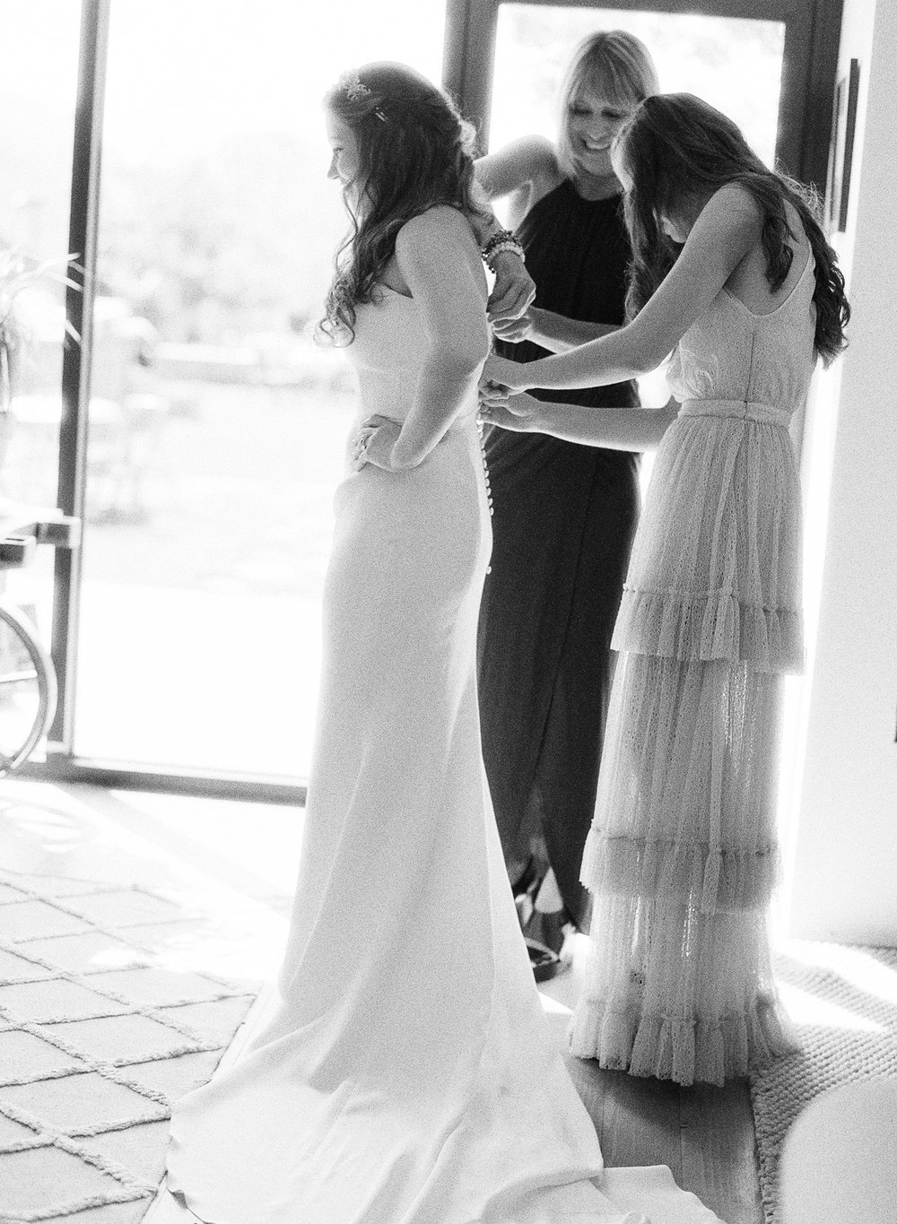 The bride's sister helps her with her gown before the Napa ranch wedding ceremony; Sylvie Gil Photography