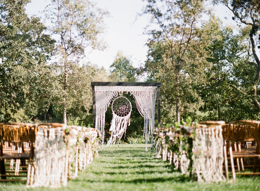 A giant dreamcatcher and macrame hanging decorates the ceremony space at a Napa Valley ranch; Sylvie Gil Photography