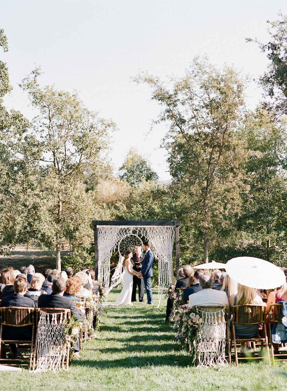 The bride and groom say their vows under a macrame-draped arbor in front of a dreamcatcher; Sylvie Gil Photography