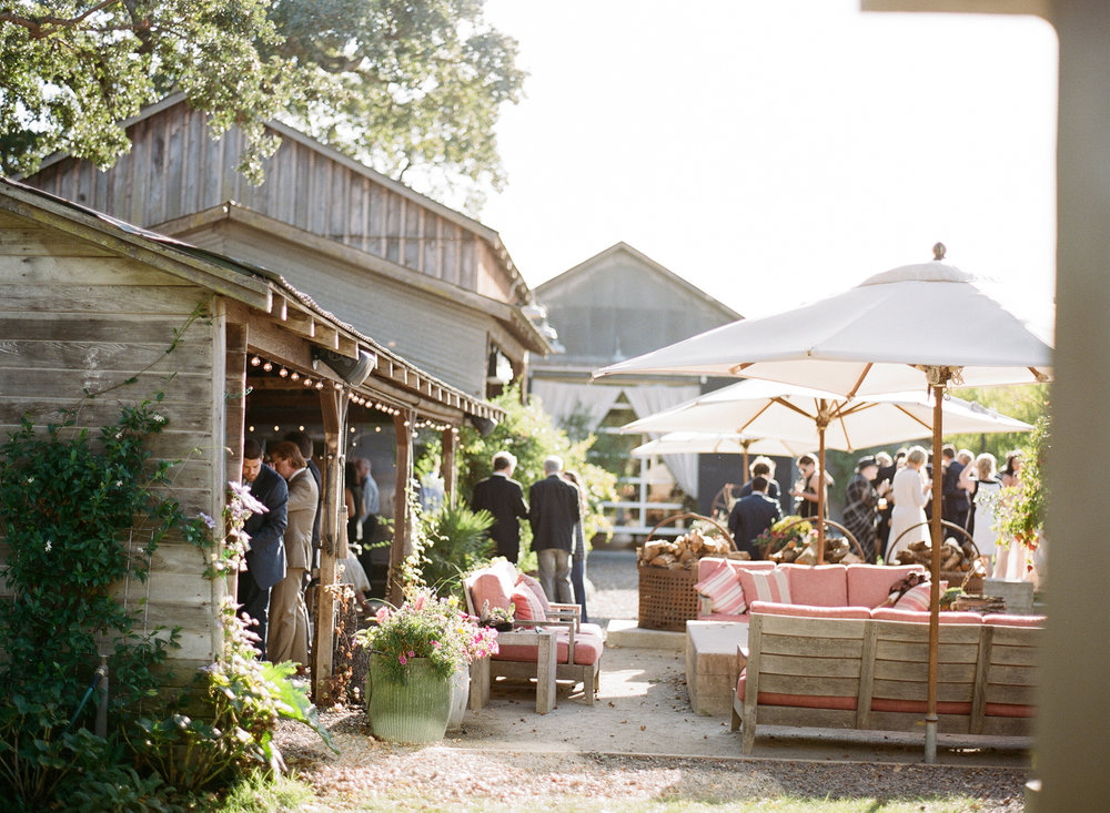Guests mingle among rustic string-lit barns during the reception cocktail hour; Sylvie Gil Photography