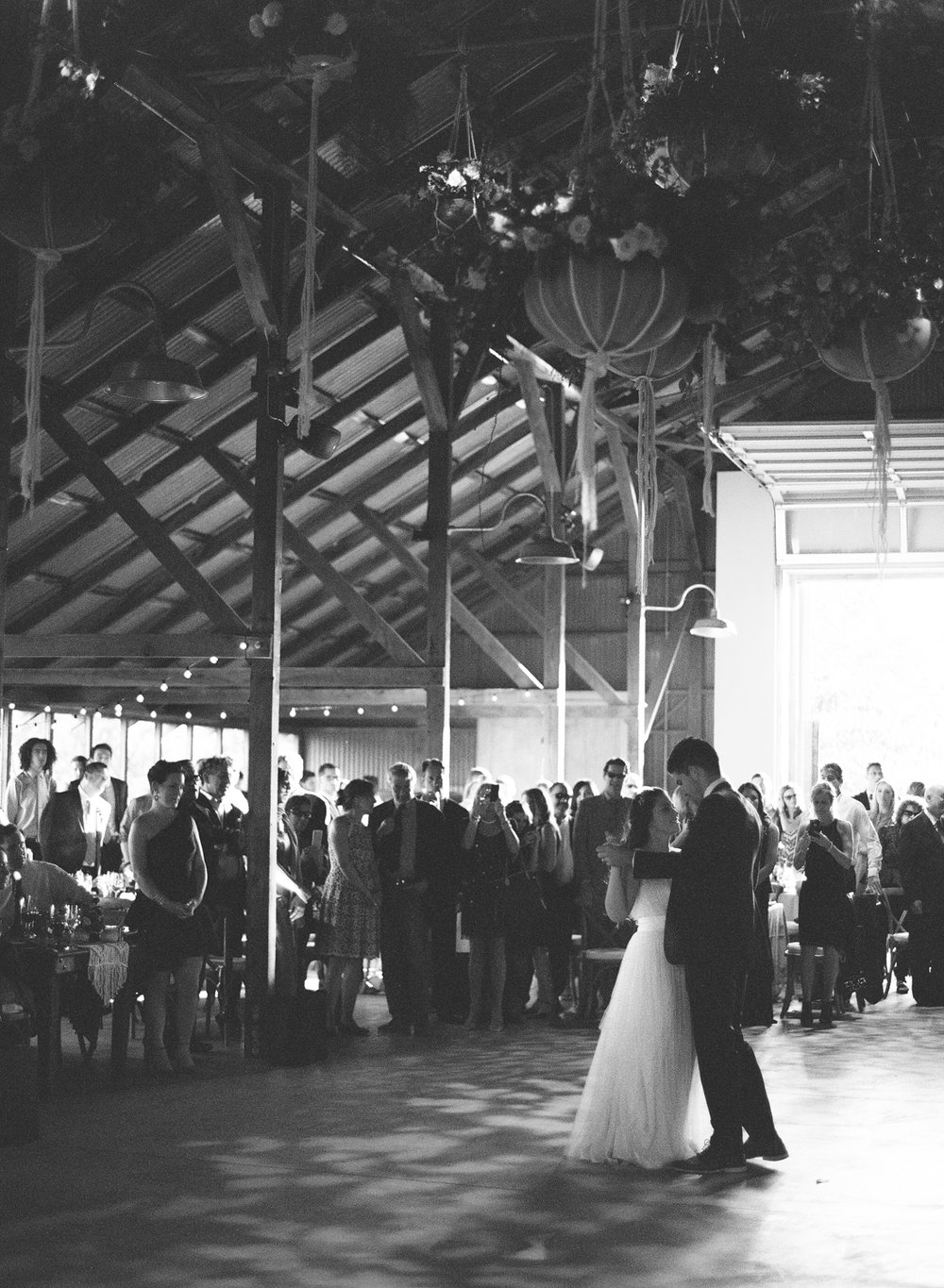 The bride and groom take their first dance in an airy barn in Napa Valley; Sylvie Gil Photography