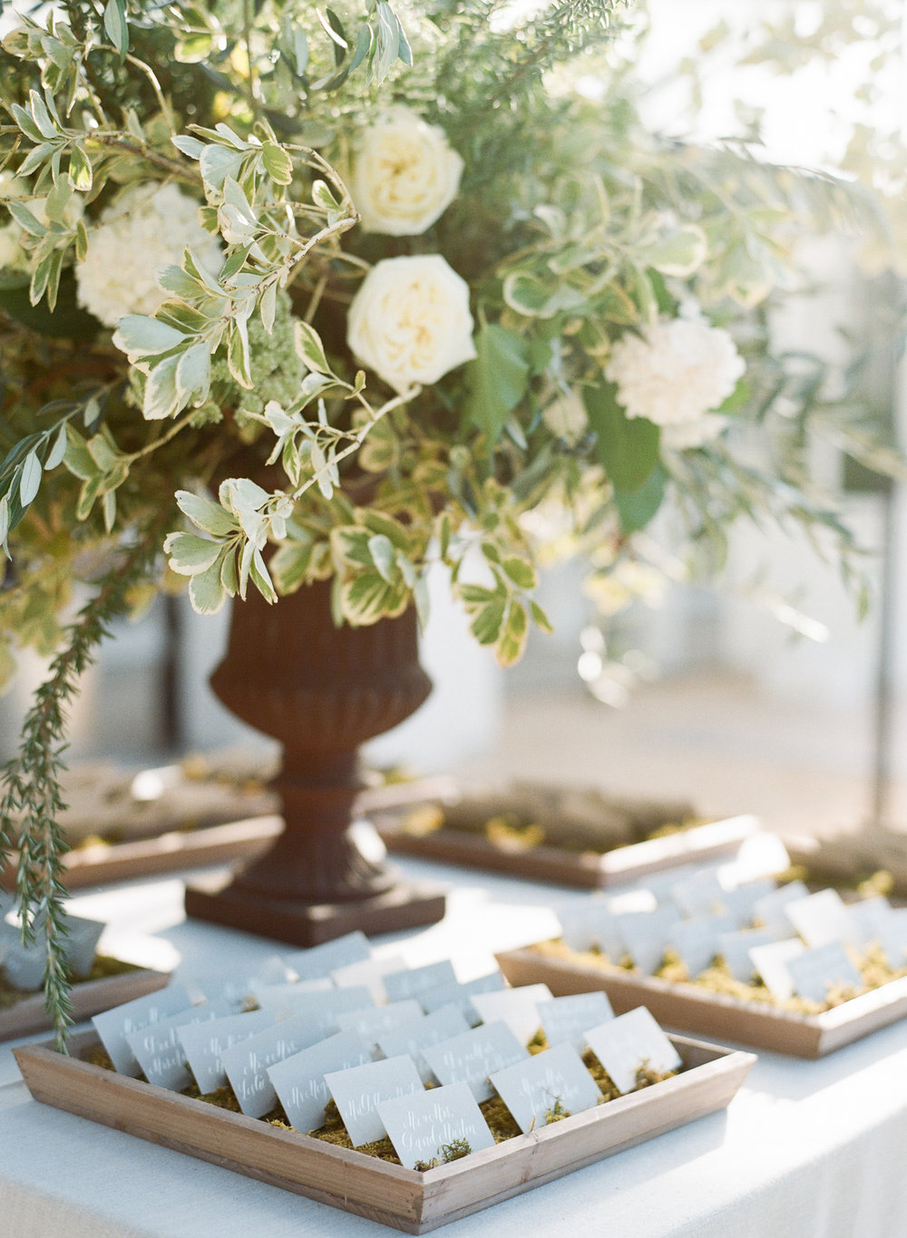 Olive branch floral arrangement at a table holding place cards; Sylvie Gil Photography