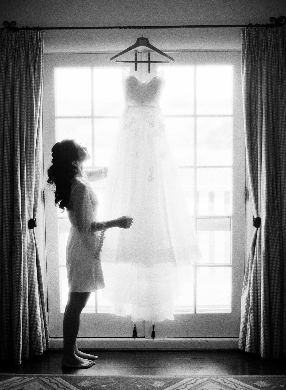The bride admires her Monique Lhuillier wedding gown before the ceremony in Carmel; Sylvie Gil Photography