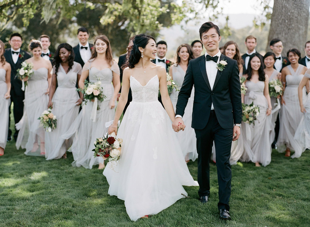 Bridesmaids and groomsmen follow the bride and groom toward the camera before the wedding ceremony in Carmel, California; Sylvie Gil Photography