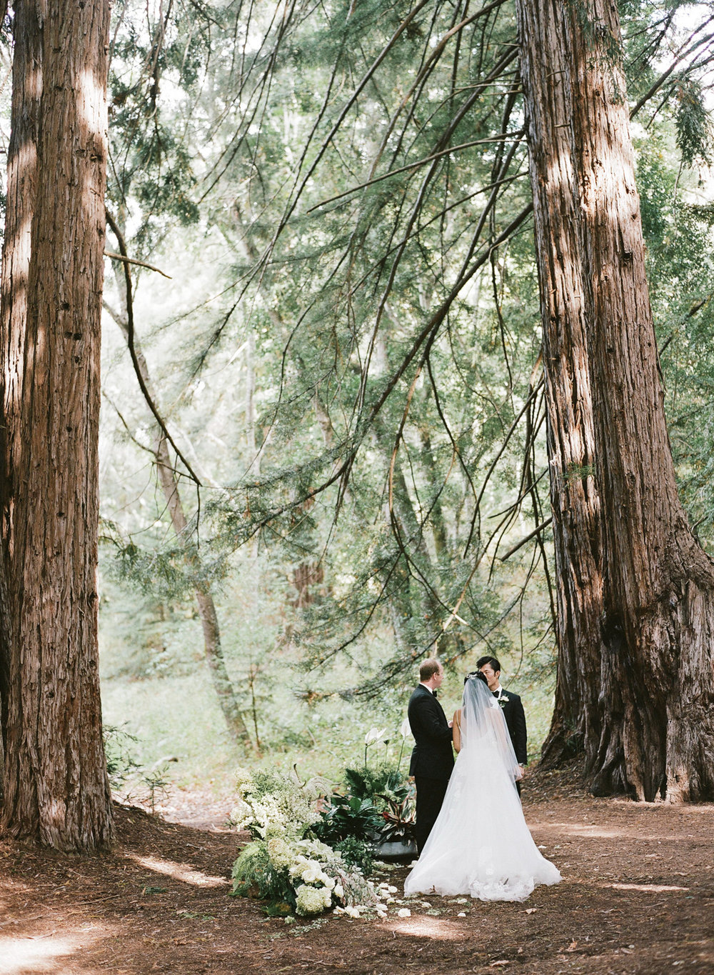 Bride and groom during a forest ceremony in the Santa Lucia Preserve in Carmel, California; Sylvie Gil Photography