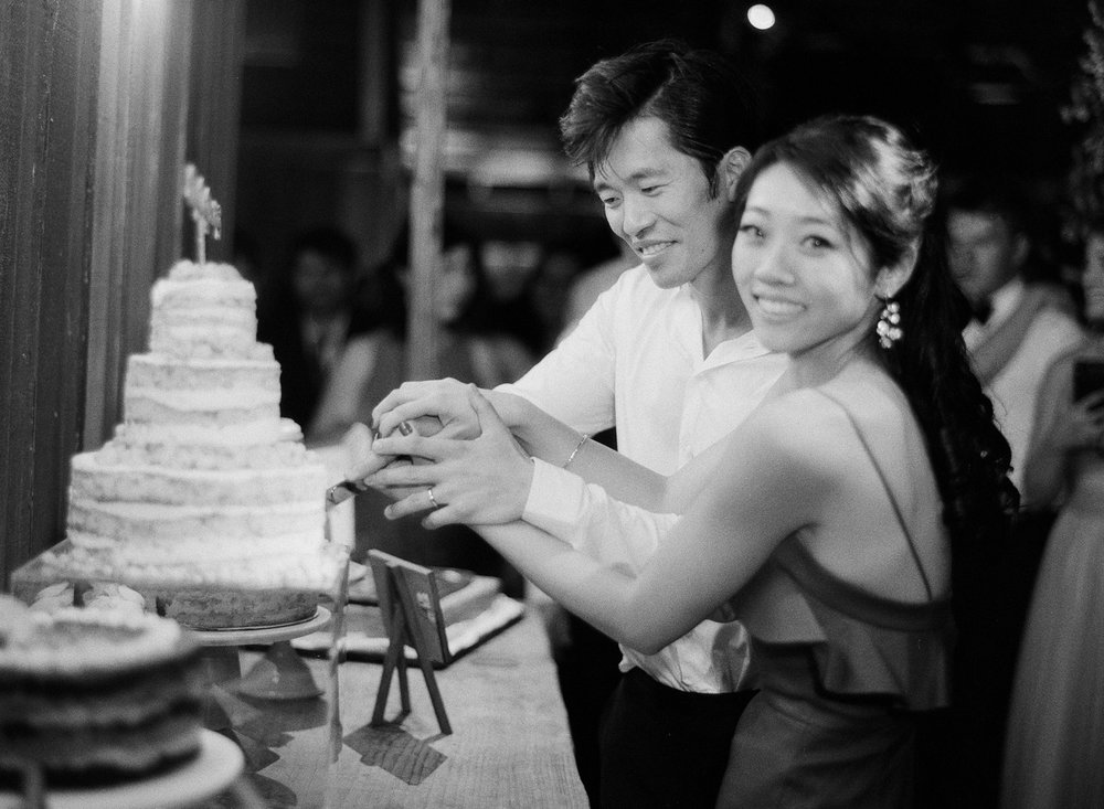 Bride and groom cut their Momofuku wedding cake at their barn wedding reception at the Santa Lucia Preserve; Sylvie Gil Photography