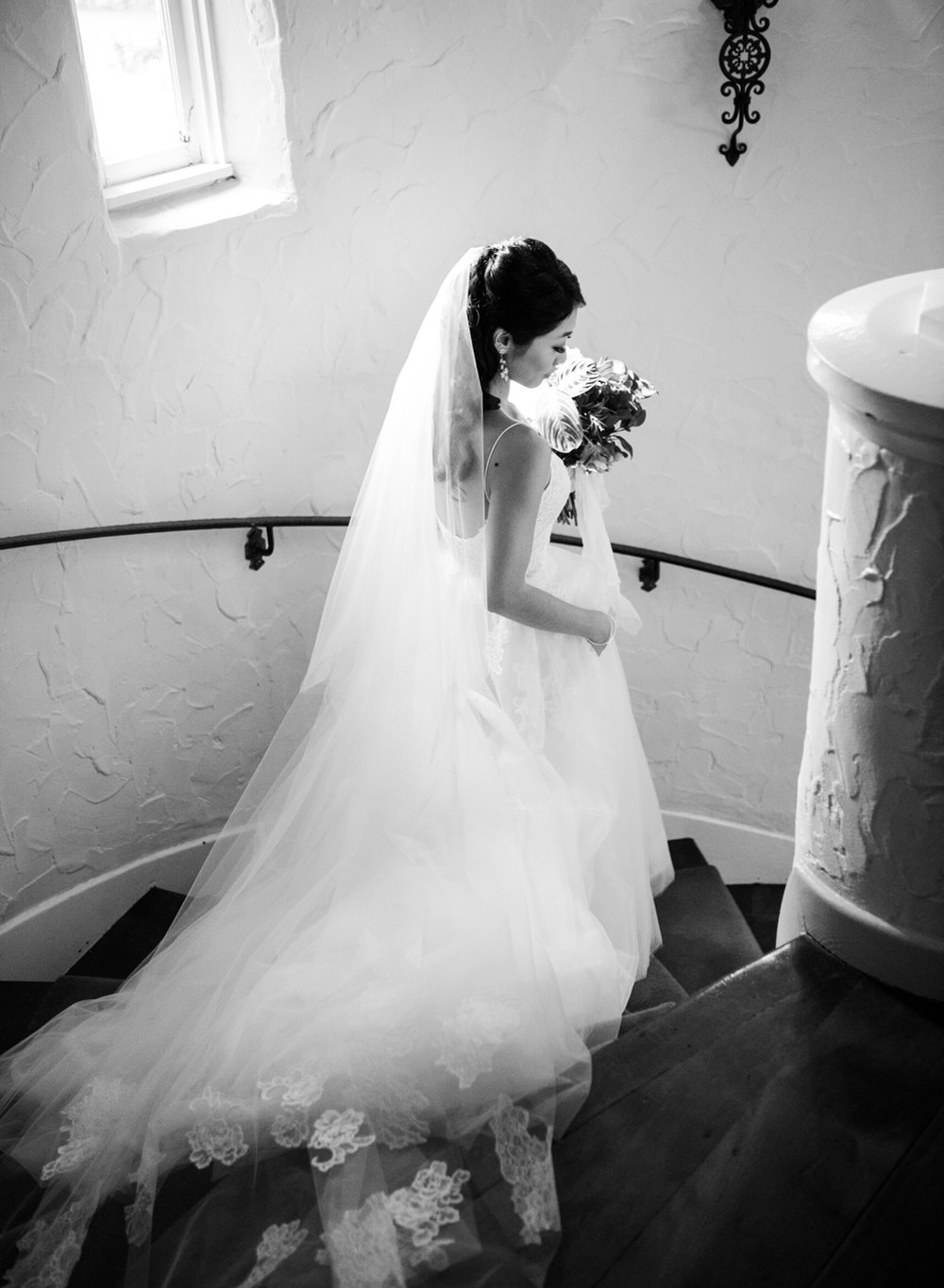 The bride walks down the stairs of the Santa Lucia Preserve ranch house before her wedding ceremony; Sylvie Gil Photography