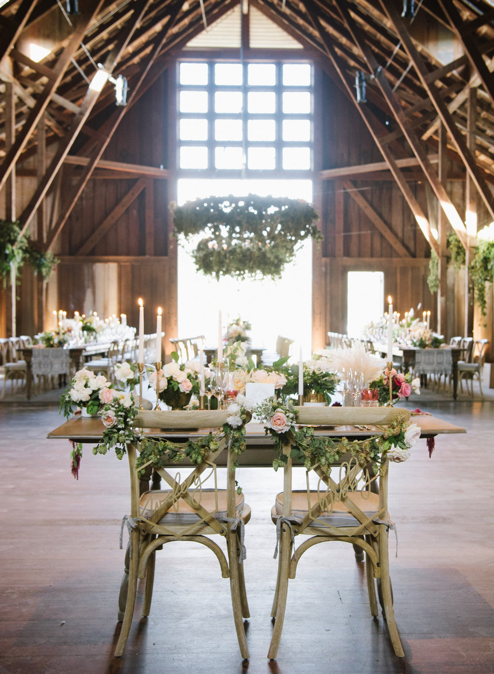 A couple table decorated with pampas grass and blush florals in a wedding reception barn in Carmel, California; Sylvie Gil Photography