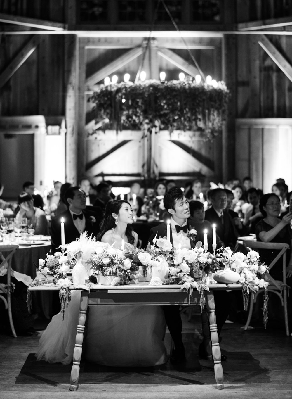 Bride and groom look on during toasts at the wedding reception in Carmel, California; Sylvie Gil Photography