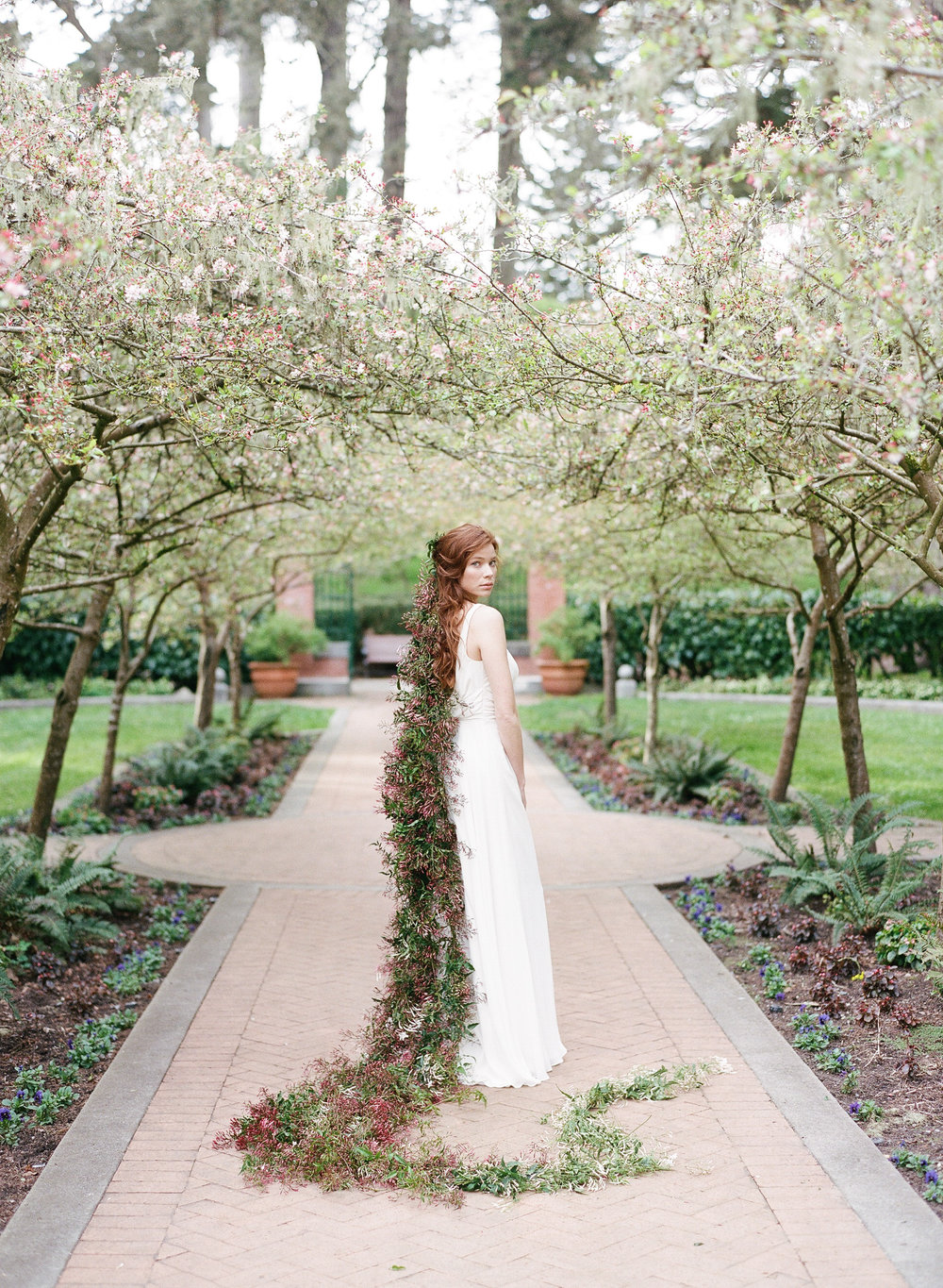 A bride stands in a San Francisco garden with a long garland of jasmine blossoms in her hair; Sylvie Gil Photography
