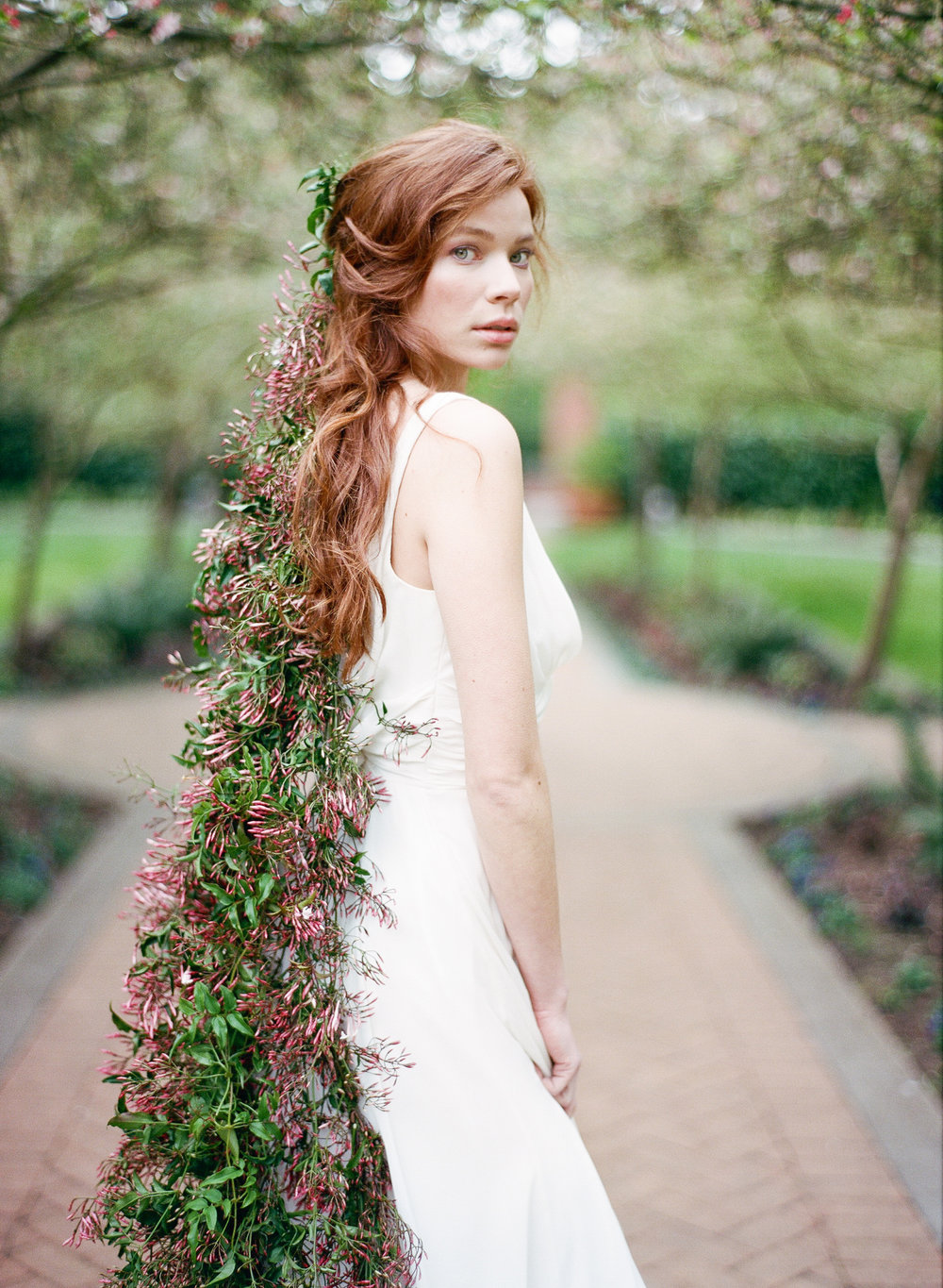 A bride looks over her shoulder, with a thick jasmine garland pinned into her hair; Sylvie Gil Photography