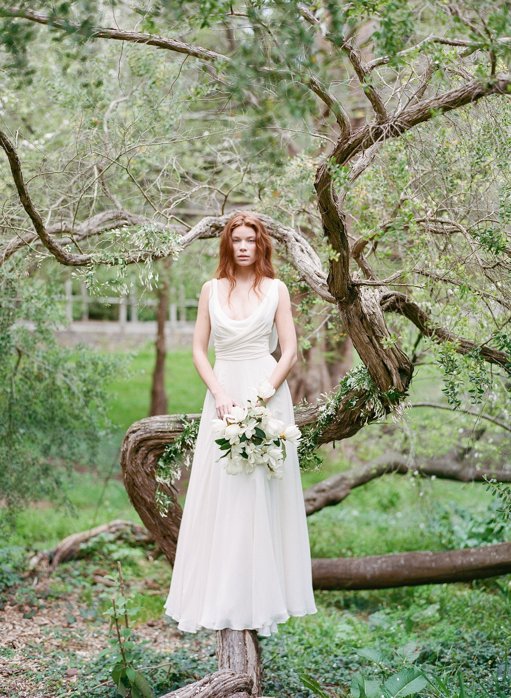 A bride stands barefoot in a tree with loose hair and a gardenia bouquet; Sylvie Gil Photography