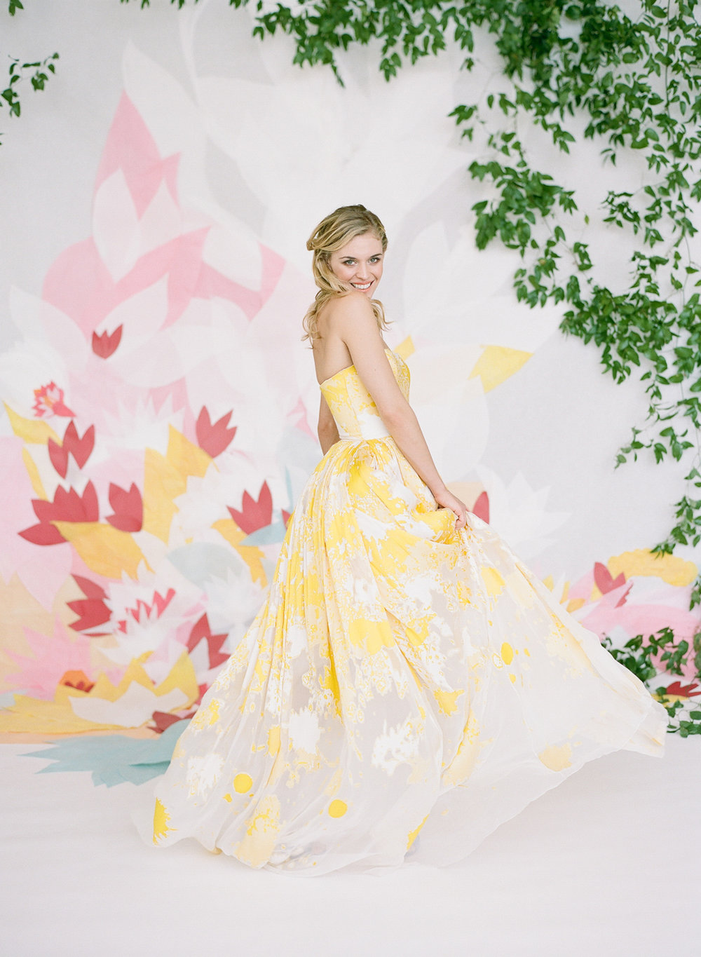 A colorful bride twirls in a yellow painted gown in front of paper flower backdrop; Sylvie Gil Photography