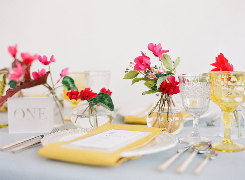 Bright pink and yellow table settings with dainty begonia floral arrangements; Sylvie Gil Photography