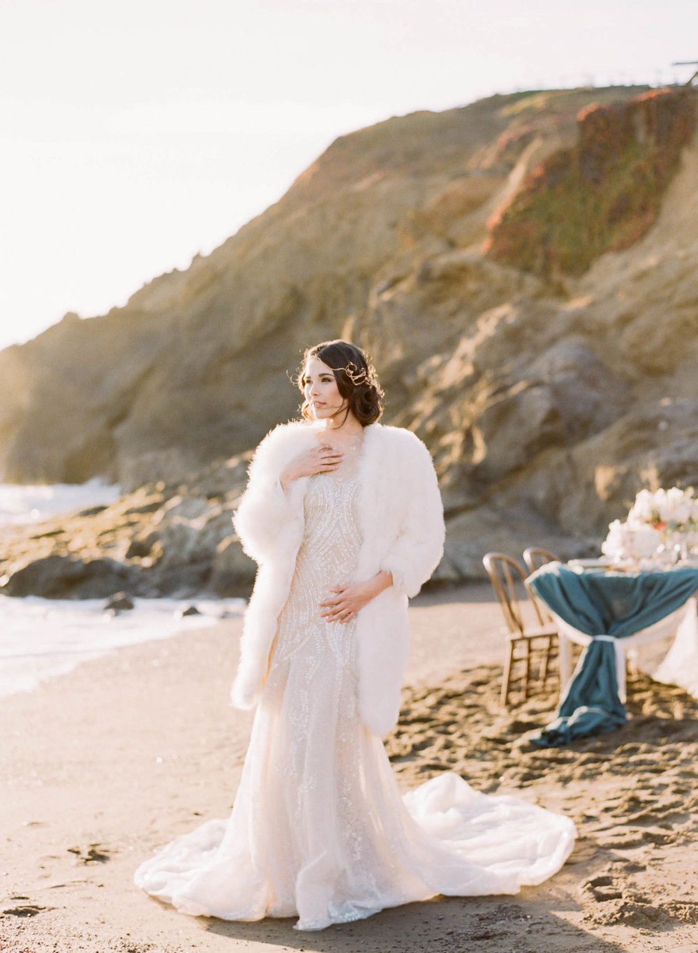 A beach bride in a 1920's gown and white fur coat in California; Sylvie Gil Photography