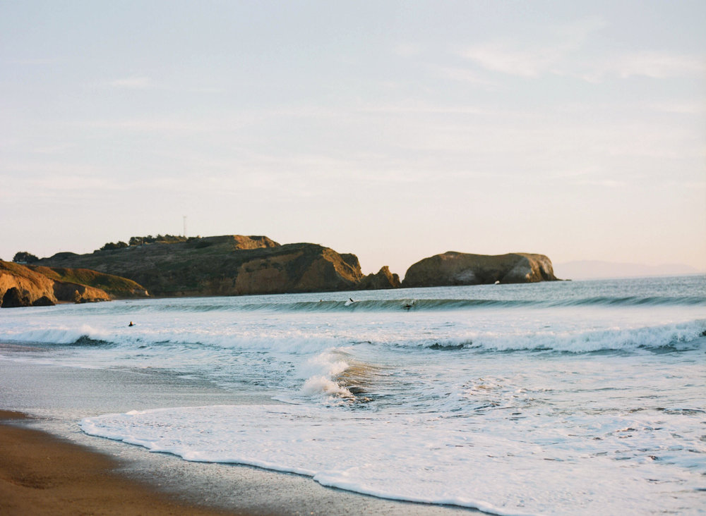 Surfers swim near a California beach at sunset; Sylvie Gil Photography