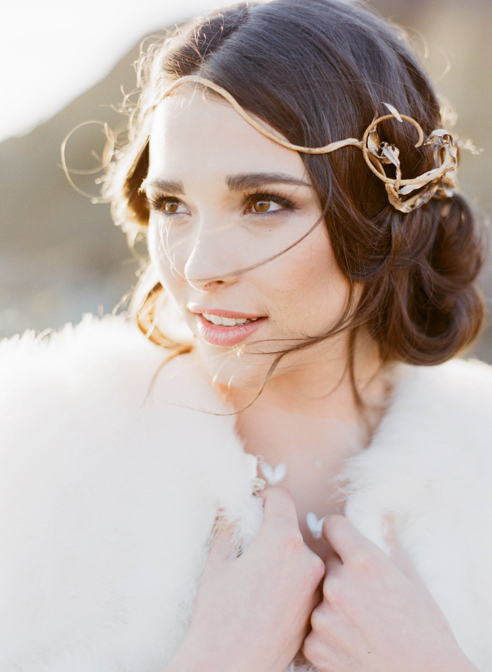 A beautiful bride on a California beach wearing a wrought gold headpiece and a white fur stole; Sylvie Gil Photography
