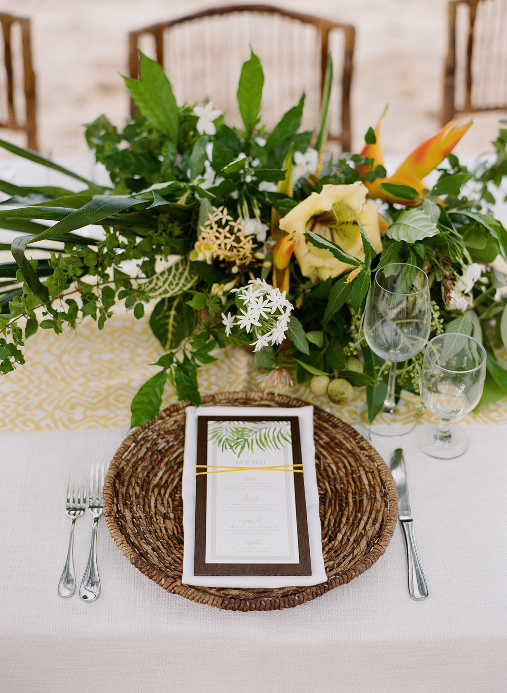 A wicker placemat and tropical flowers for an intimate beach wedding reception in Montego Bay, Jamaica; Sylvie Gil Photography