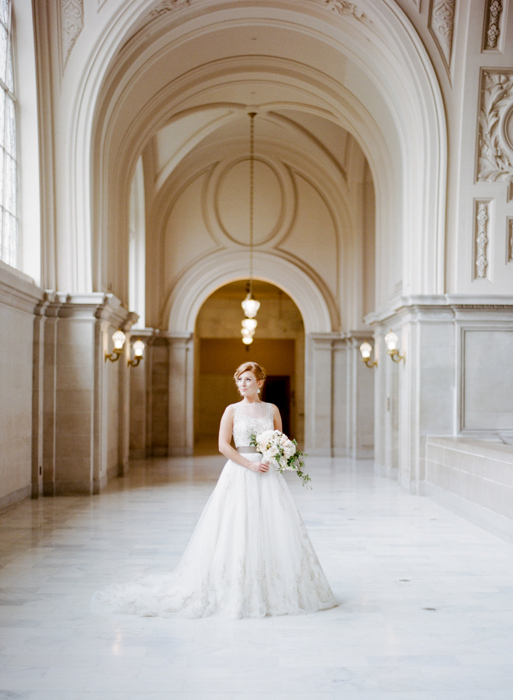 A bride stands in the mezzanine of San Francisco City Hall; Sylvie Gil Photography