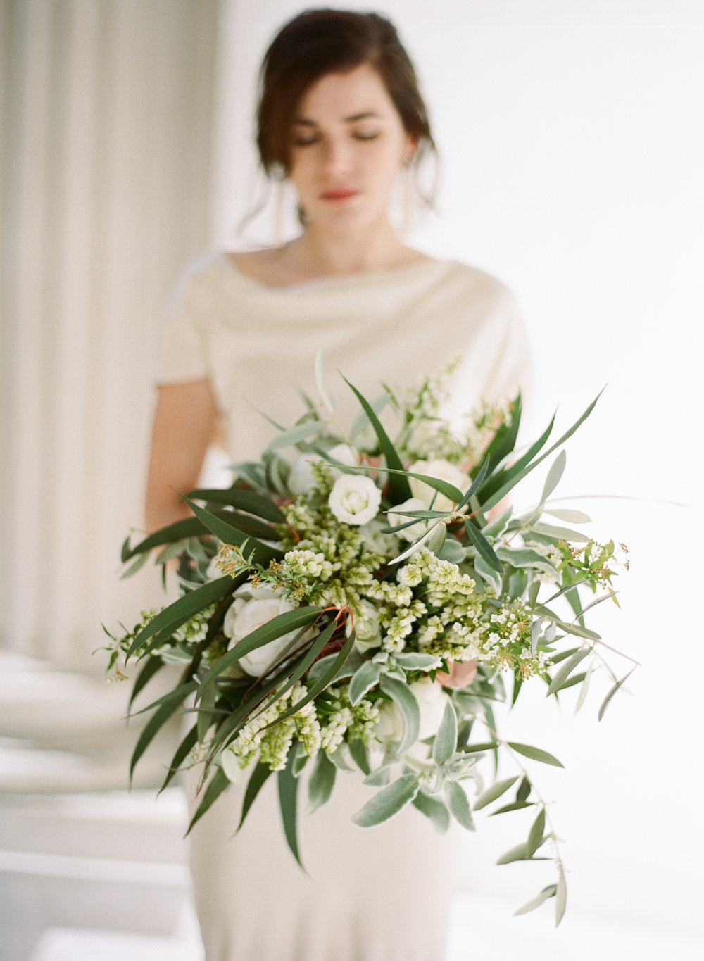 A bride holds a fern and eucalyptus bouquet at Pavillon de la Musique in Paris; Sylvie Gil Photography