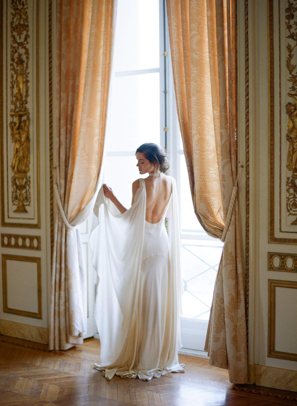A Parisian bride stands at the window in Pavillon de la Musique in Paris, France; Sylvie Gil Photography