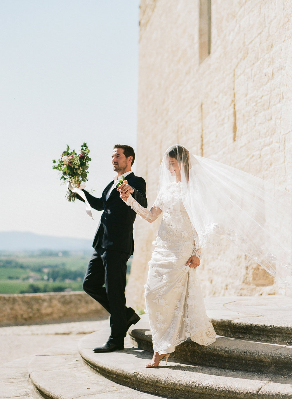 A bride and groom walk out of a village church in Provence, France, just married; Sylvie Gil Photography