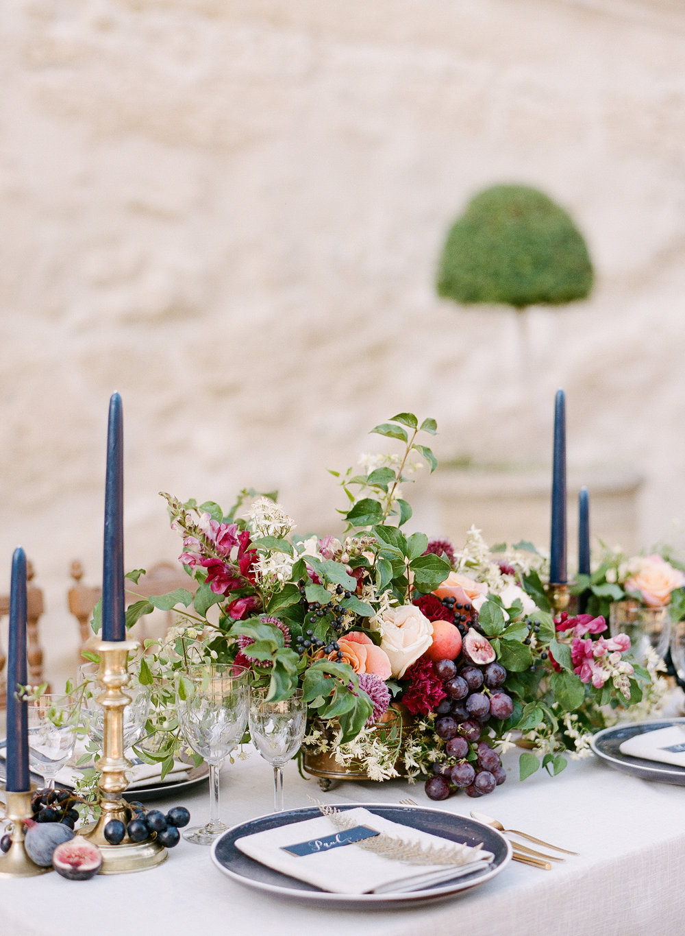 A navy and gold reception table setting with fresh fruit and burgundy florals; Sylvie Gil Photography