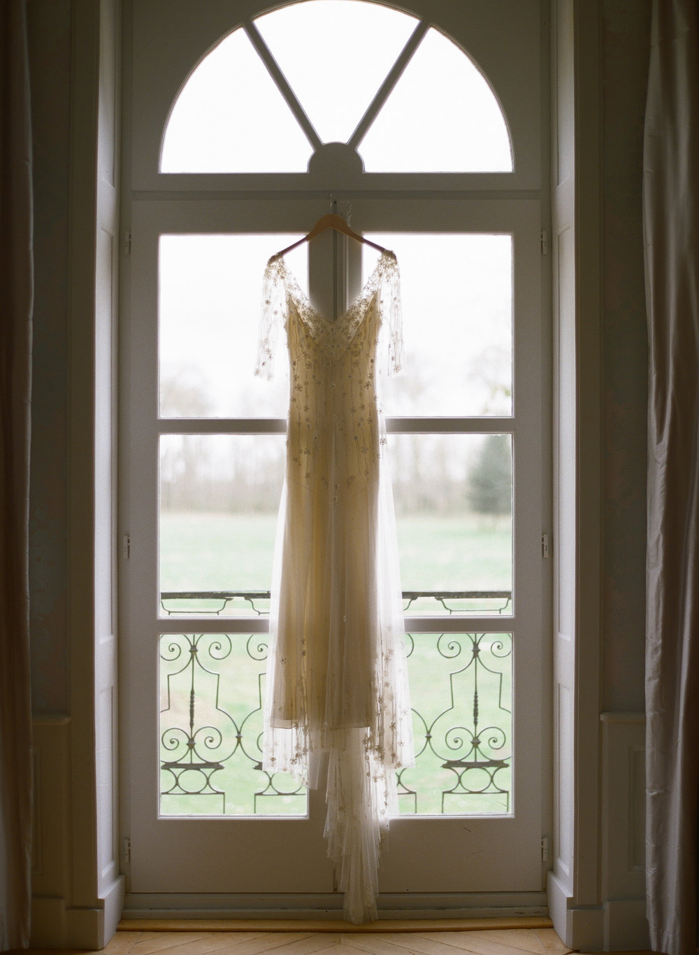 A wedding gown hangs in the window at Chateau de Varennes; Sylvie Gil Photography