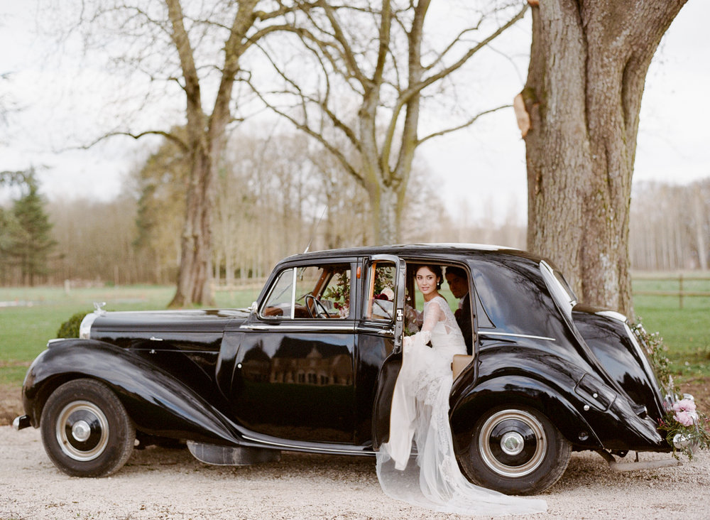 Bride and groom leave their wedding at Chateau de Varennes in Burgundy, France, in a vintage getaway car; Sylvie Gil Photography