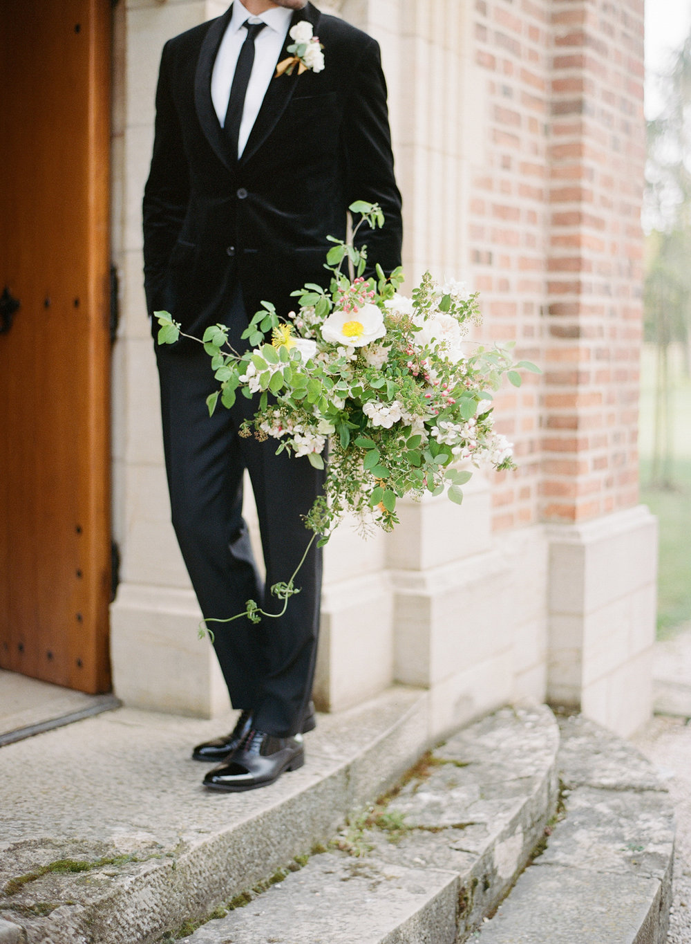 A groom stands with the bride's bouquet outside a chapel in Burgundy, France; Sylvie Gil Photography