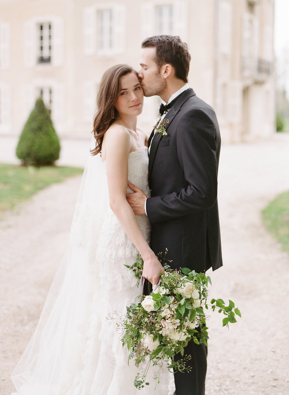 A groom kisses his bride after a wedding in Burgundy, France; Sylvie Gil Photography