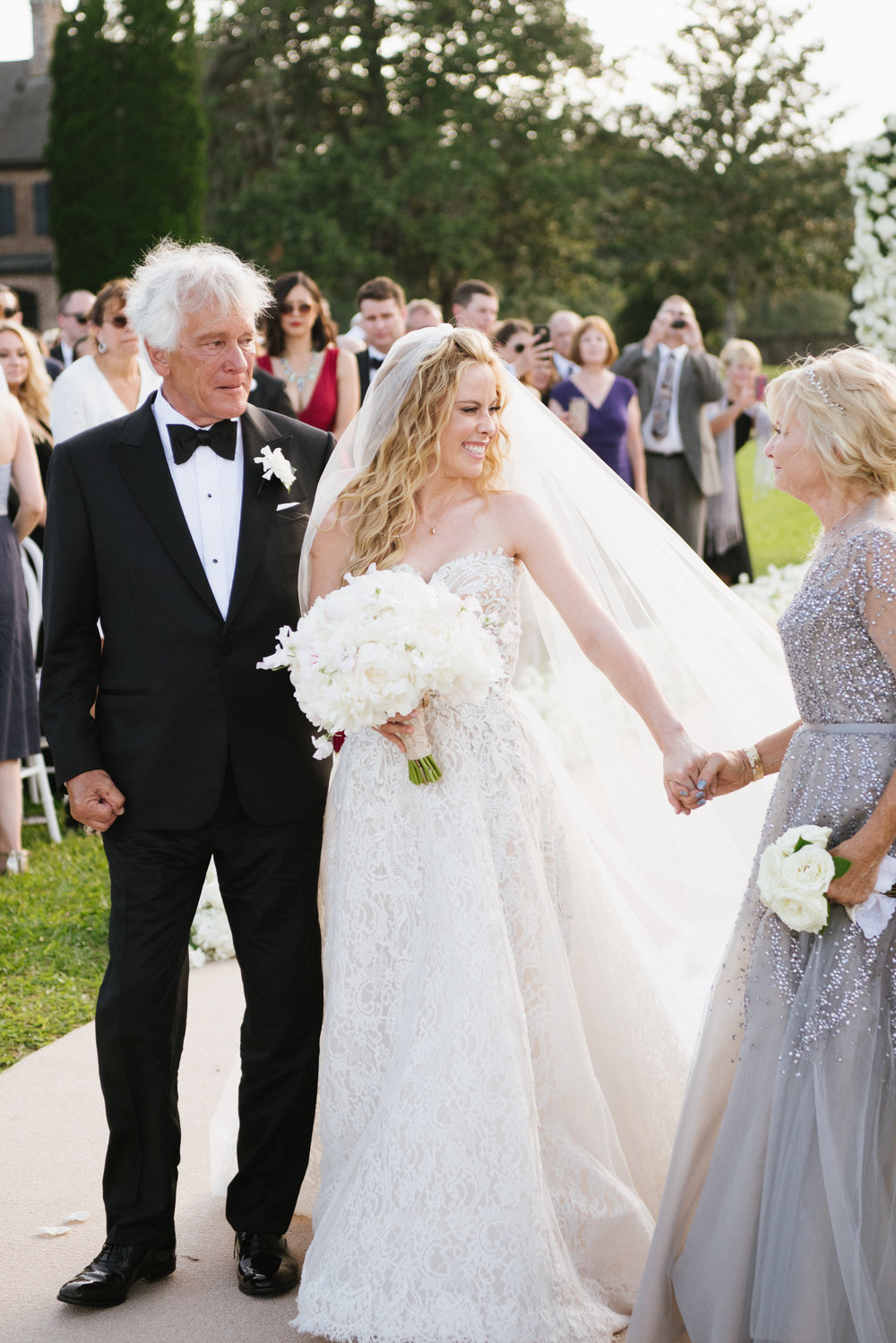 Tara Lipinski walks up the aisle with her parents on her wedding day in Charleston; Sylvie Gil Photography