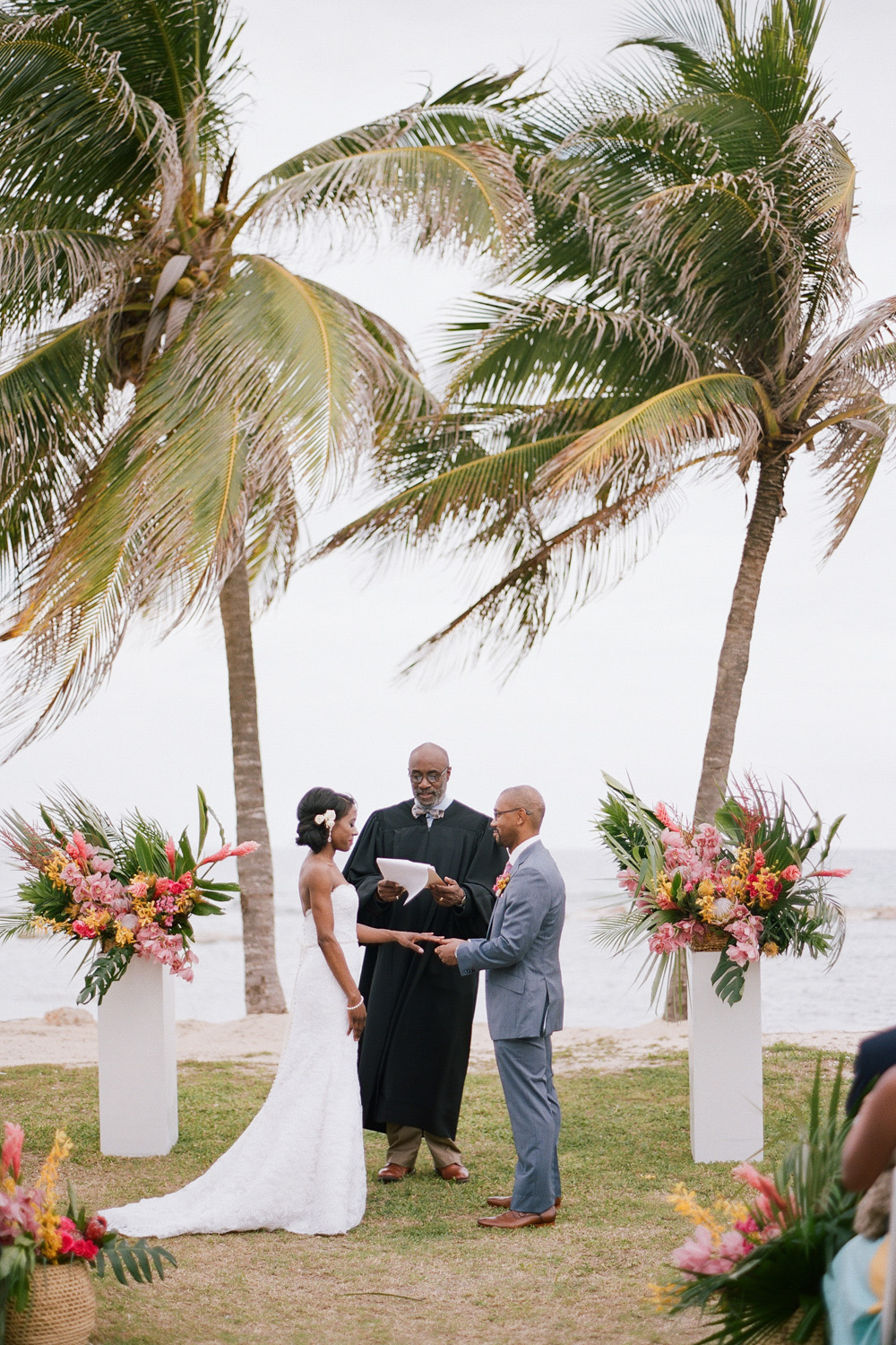 A beach ceremony in Montego Bay, Jamaica under two palms; Sylvie Gil Photography