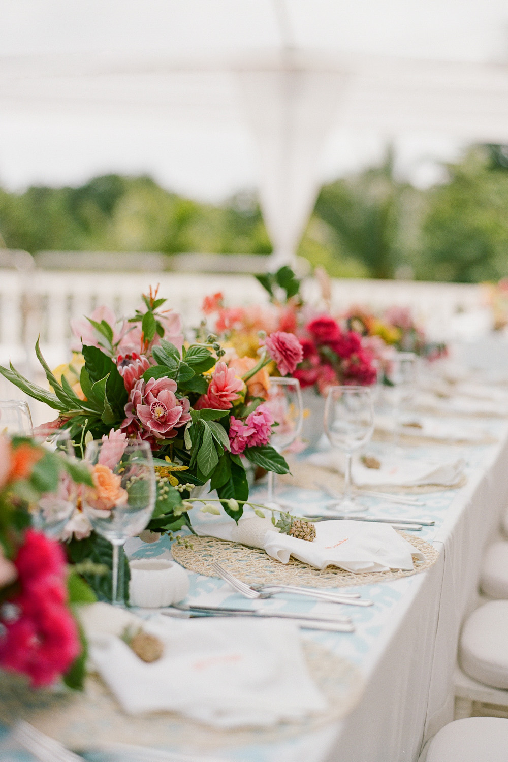 Deep pink and coral tropical blooms at a wedding reception in Montego Bay, Jamaica; Sylvie Gil Photography